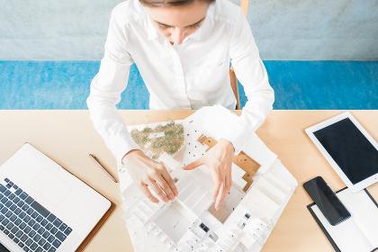 建物の模型を見つめる女性(不動産・都市開発)
