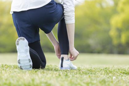 靴紐を結び運動の準備をする若い女性
