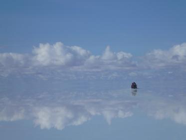 ボリビアのウユニ塩湖にて水面に鏡のように反射する景色の中をドライブする車