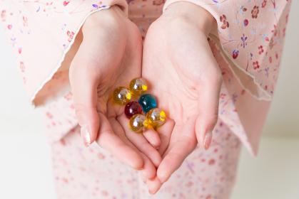 ビー玉を持つ着物を着た女性の手