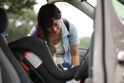 子供をチャイルドシートに乗せる母親