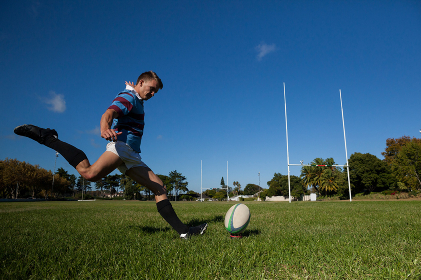 Full length of rugby player kicking ball for goal