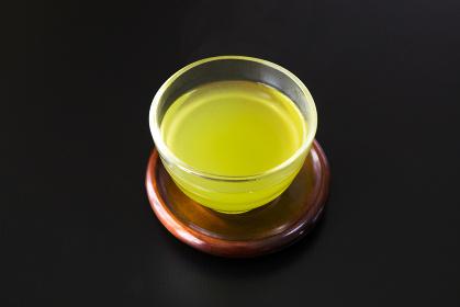 黒い背景のガラスの湯吞みに入った緑茶