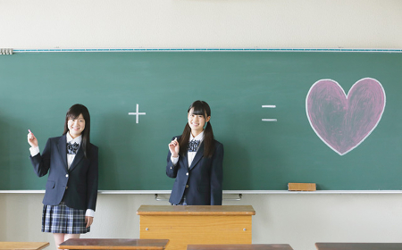 教室の黒板にハートを描く女子高生