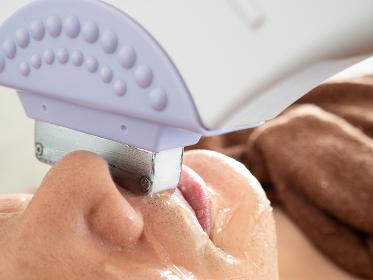 鼻の下のヒゲ脱毛の施術を受ける男性