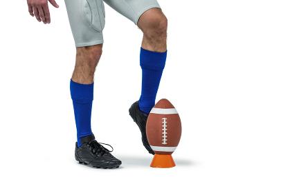 American football player kicking ball