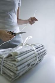 新聞紙を束ねて余ったビニール紐を鋏で切る女性