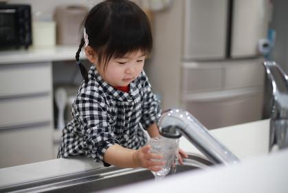 コップに水を注ぐ女の子