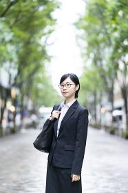 街路樹が並ぶ通りに立つスーツ姿の若い女性