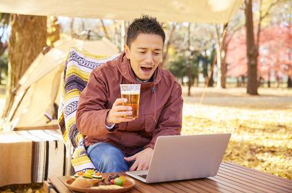 キャンプ場でオンライン飲み会を楽しむ日本人男性