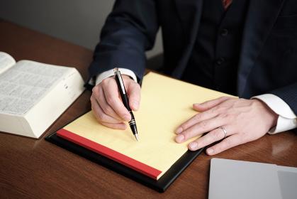 リーガルパッドにメモをする男性弁護士の手元