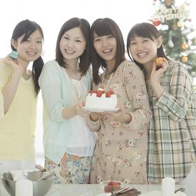 ケーキとクリスマスグッズを持ち微笑む4人の女性