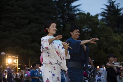 盆踊りを楽しむ浴衣姿のカップル