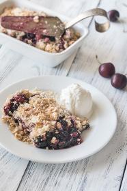 Portion of berry crumble with vanilla ice cream