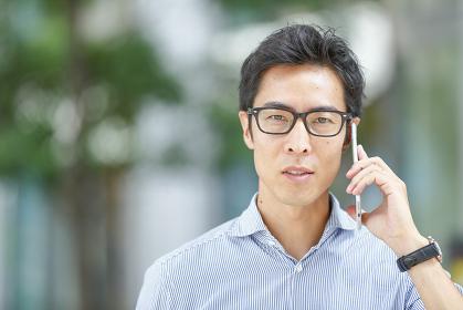 スマートフォンで通話する眼鏡の日本人男性