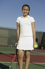 Young female tennis player standing on court with racket and ball portrait
