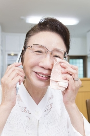 電話中に涙を流すシニア女性