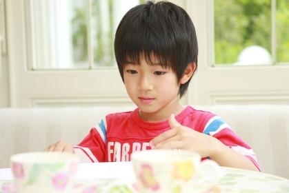 お絵かきをする赤いTシャツを着た男の子