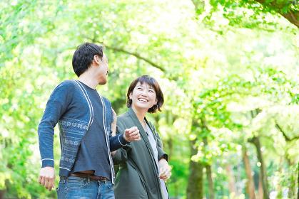 緑の豊かな公園でデートをするカップル