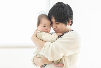 明るい部屋の中で赤ちゃんを抱っこするお父さん
