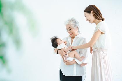 赤ちゃんを抱っこするシニア女性と見守る女性たち