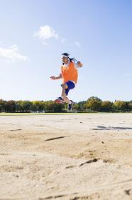 走り幅跳びをする高校生