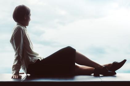 空を見つめる女性(全身・シルエット)