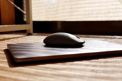 畳の上のパソコンとマウス 日除けによる日光の縞模様
