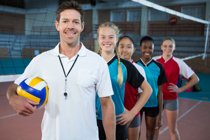Male coach and volleyball players standing in a row