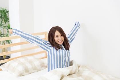 パジャマを着た女性 ベッド 笑顔