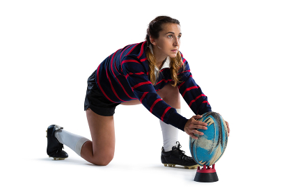 Full length of young female athlete keeping rugby ball on tee