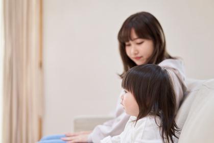 テレビを見るアジア人の女の子とお母さん