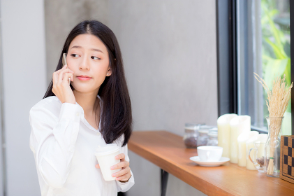 Beautiful young asian woman talking phone and smile in the coffe