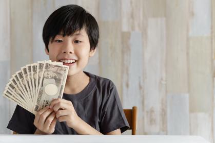 1万円札を持って笑うカメラ目線の小学生の男の子