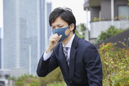咳をするカラーマスクをつけた日本人ビジネスマン