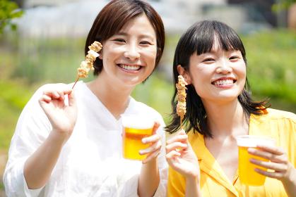 焼き鳥とビールを持つ女性