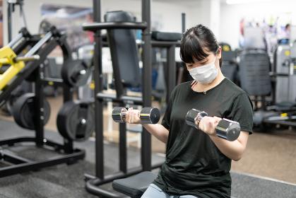 マスクしてフィットネスジムで筋トレをする女性