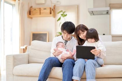 ソファに座ってのタブレットを見るアジア人ファミリー