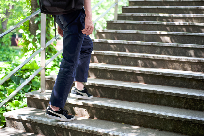 爽やかな新緑の階段を上がる男性