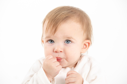 Baby's face with the hand in the mouth
