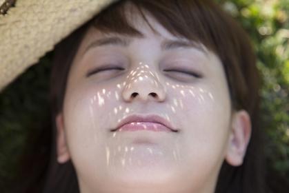 草原で仰向けに寝る日本人女性の顏