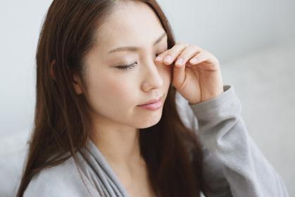 目をこする若い日本人女性