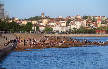 青島(中国)の海岸、ドイツ租借地時代の街並みと、磯遊びの人混み