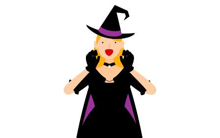 ハロウィンの仮装、魔女姿の女性が両手を構えて驚かせるポーズ