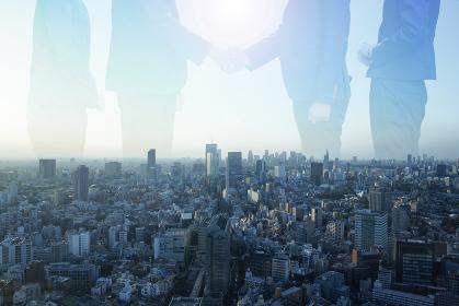 握手するビジネスマンと都市の合成写真