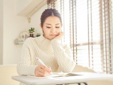 学校の課題をするアジア人女性