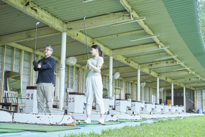 ゴルフ場でゴルフを教える男性と教わる女性