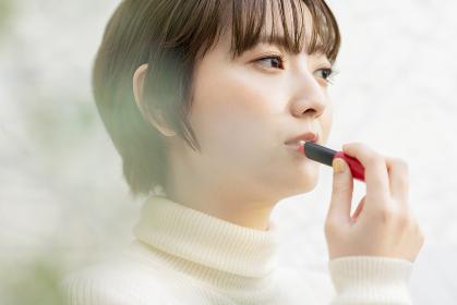 口紅を塗るアジア人の若い女性