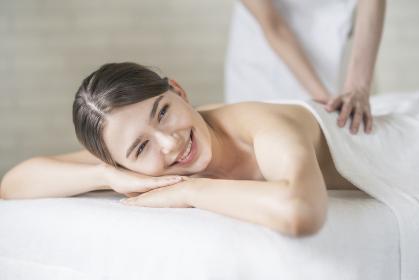 明るい雰囲気のエステサロンでマッサージを受ける若い女性