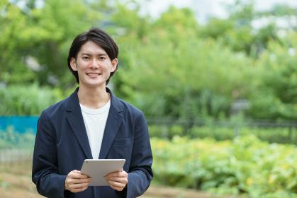 畑を管理する若い男性・ITとAIの活用